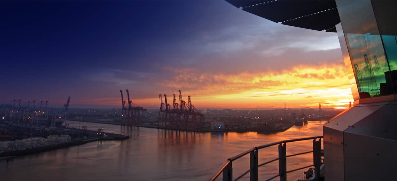 sunset view of the port of melbourne with cranes next to the victorian harbour