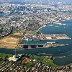 aerial view of the port of melbourne with the city buildings in the background