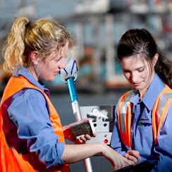 ladies in high vis vests pointing at tablet discussing port of melbourne tasks