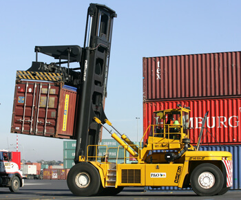 stevedoring workers fork lift driving and moving shipping container