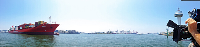 panoramic view of the port of melbourne containing a cargo vessel entering the harbour